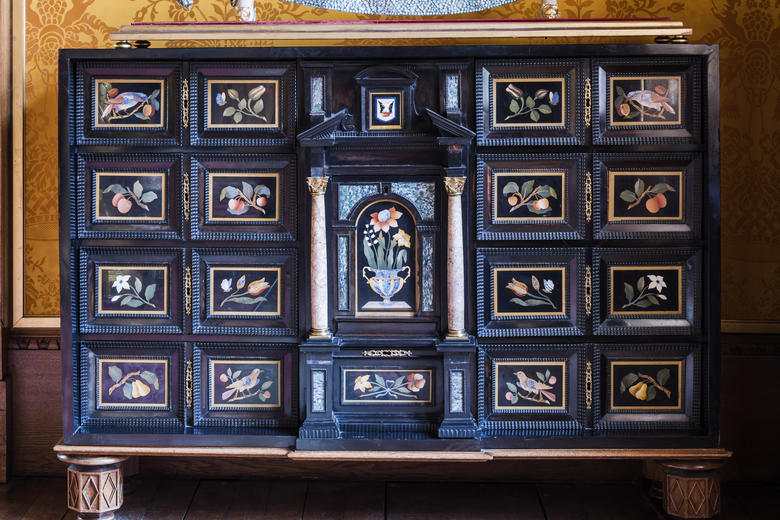 Blue decorated cabinet in front of a yellow tapestry.
