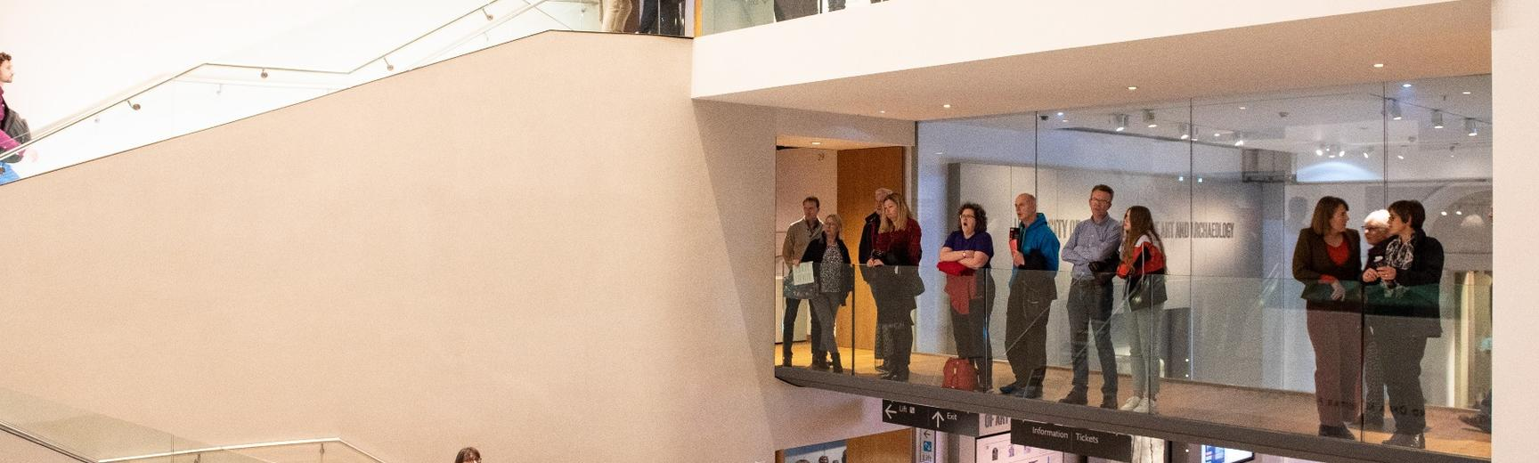 People standing on a balcony at the Ashmoleum Museum viewing an exhibition that is out of frame