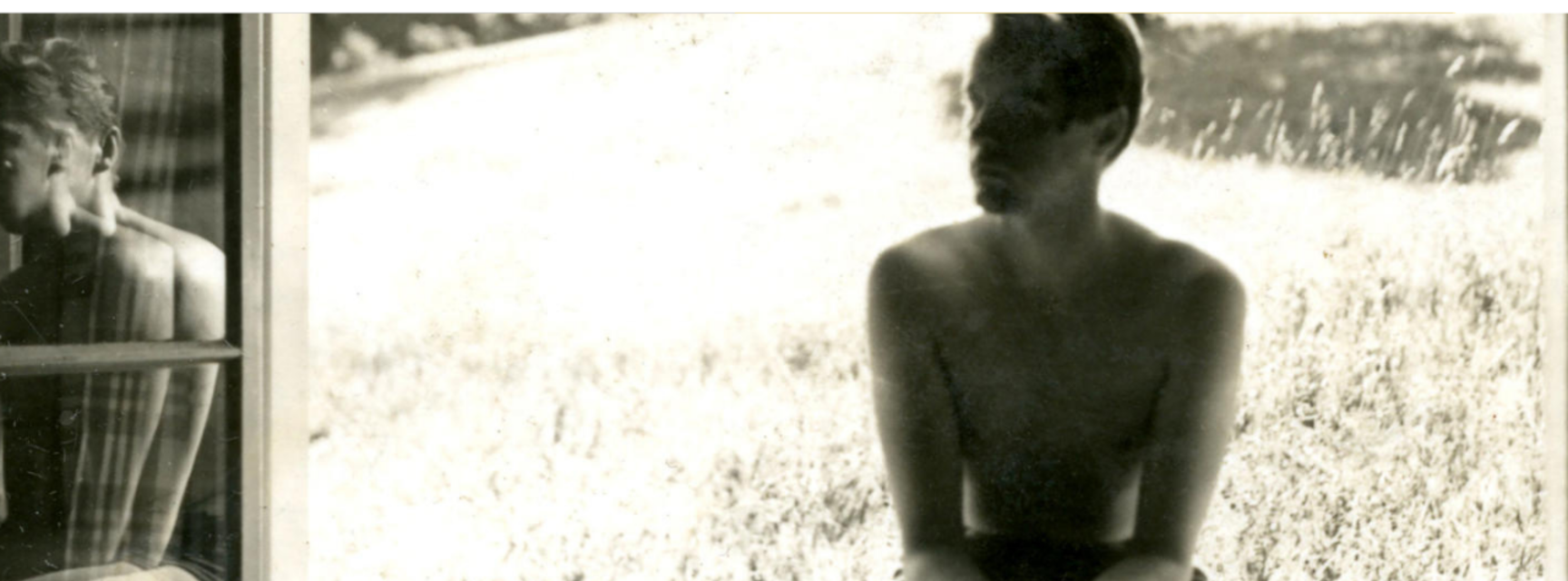 Black and white photo of a shirtless man sat in a doorway with grass behind him. His reflection is visible to his left.