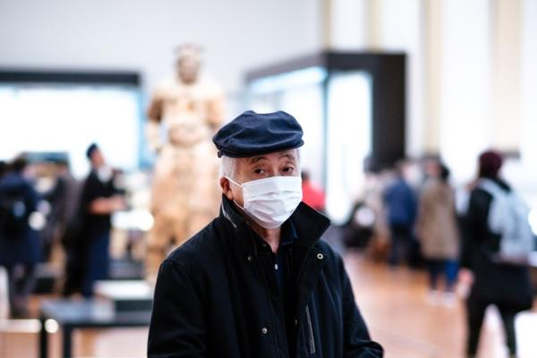 man in face mask standing in a gallery