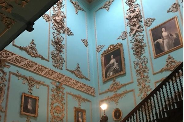 Photo from the bottom of the stairs looking up. The walls are painted in a light blue and decorated with paintings and golden mouldings.