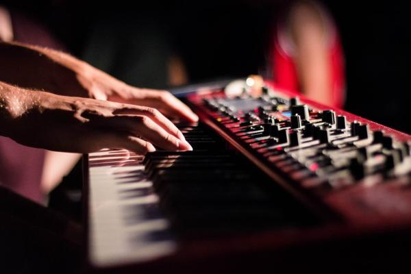 Hands playing piano keyboard with dark background