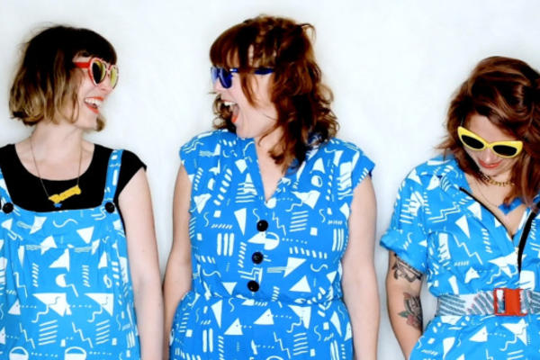 Three women in blue tunics