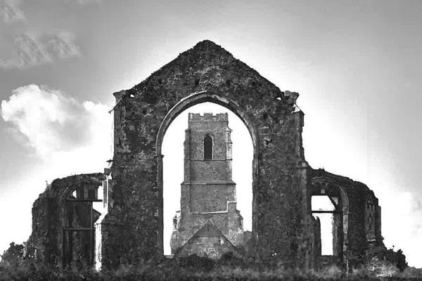 A black and white picture of the deserted church. One standing arch provides the frame for a view of the bell tower.