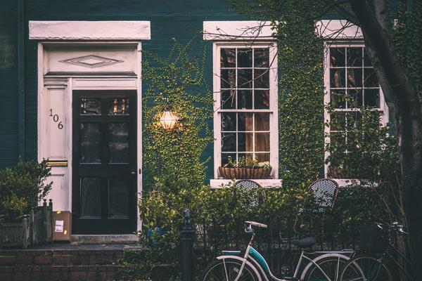 Bicycle leaning beside fence, small cottage, foliage bjqejxeyije unsplash