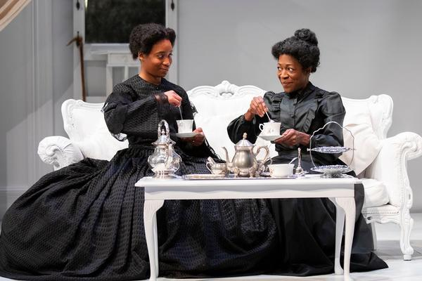 Two black women sit on a white chaise lounge drinking tea