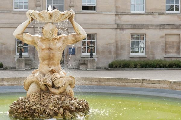 A statue of a man with water coming out of his mouth and a bowl rested on his head.