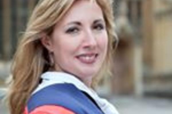Image of Nina Kruglikova wearing red and blue DPhil gown in front of the Old Bodleian Library