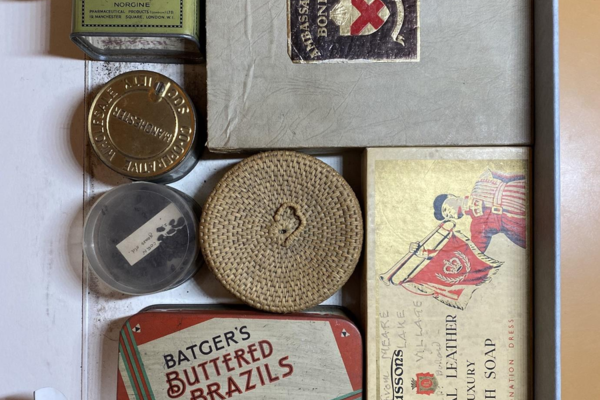 Old-fashioned metal tins and cardboard boxes originally containing nuts, soap, and medicine, in an archival box