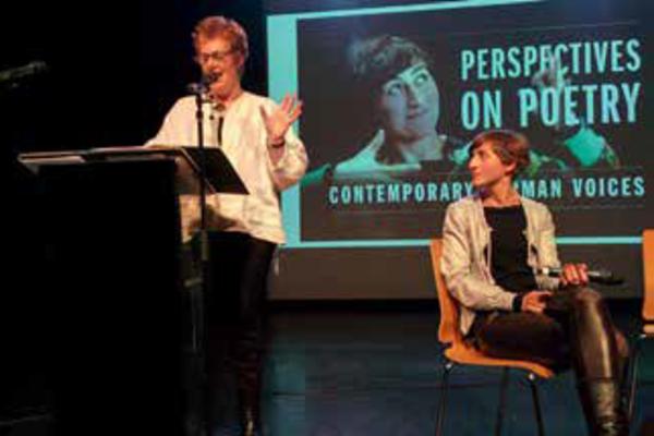 Karen Leeder (standing) and Almut Sandig (sitting) speaking at a conference regarding Mediating modern poetry