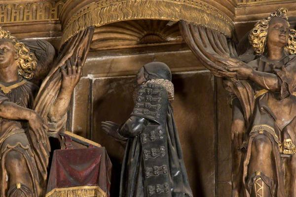 Carved wooden figure of person in long robes at a lectern