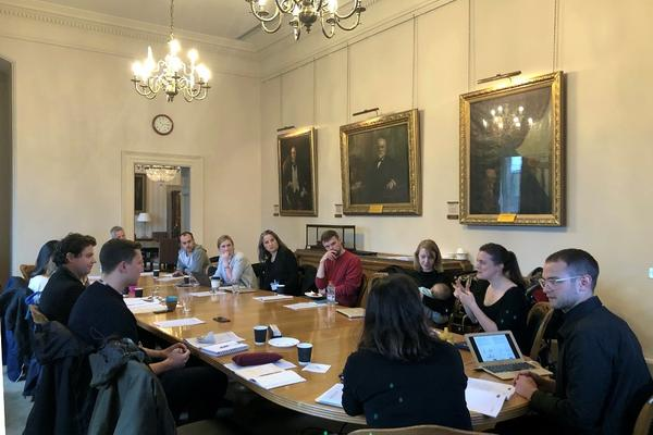 Participans sitting at an oval table during the Scoring the City Workshop in Belfast