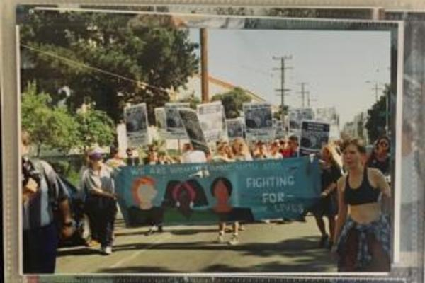 A blue banner with three female faces leads the front of a protest march along a street with people holding signs behind it