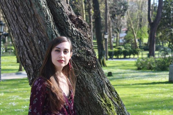 rocio riestra camacho, stood in front of a tree wearing a purple top. There are more trees and a lamppost in the background.