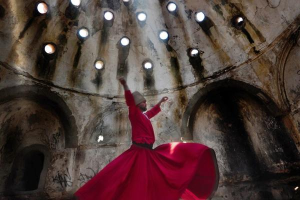Person wearing a red gown dancing in an open cathedral.