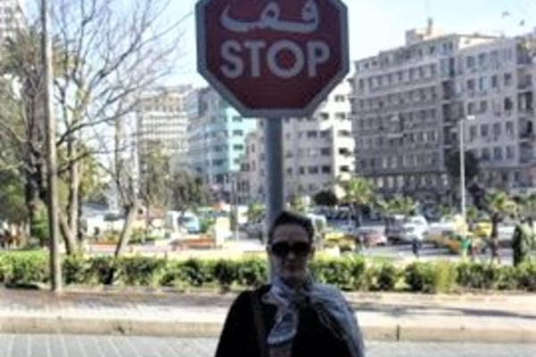 woman in black top and scarf stands under a stop sign