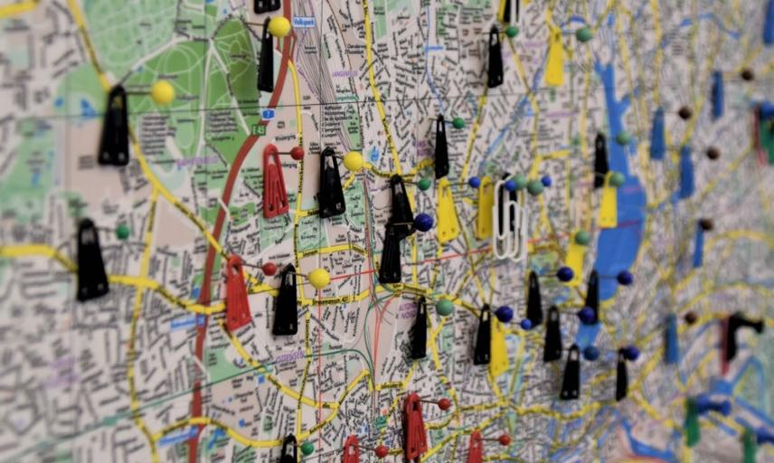 a tilted photo of a map with pins and small arrows stuck on it