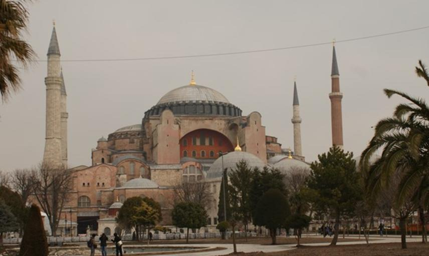 A photograph of the hagia sophia surrounded by trees with 3 people in the foreground taking a photograph