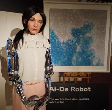 AiDa the robot standing next to her painting