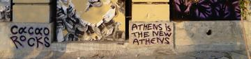 "A mural in Metaxourgeio by Cacao Rocks stating, ""Athens is the new Athens"", photo taken by the authors in July 2018."