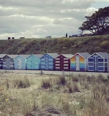 multicoloured beach sheds lined up on the beach