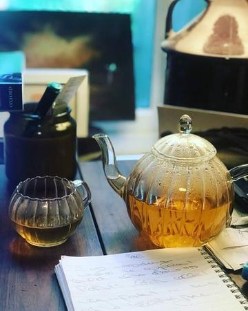 Glass teapot and cup with tea sitting on a table with open notebook in front