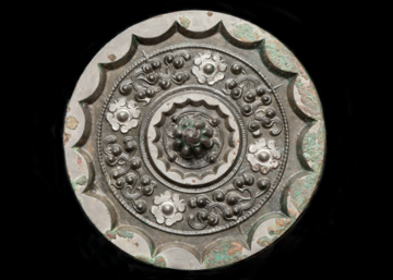 Back view of a bronze mirror decorated with star and cloud pattern. The knop at the centre of the mirror is cast as a mountain, surrounded by four small bosses and an abbreviated cloud design. The thickened rim of the mirror is cast with sixteen arcs.
