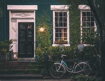 Bicycle leaning beside fence, small cottage, foliage