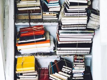 Image of stacked books and notebooks