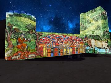 A colourful illustration of a medieval village is projected onto the side of Oxford Castle