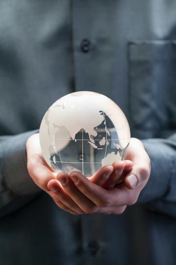 Person clutching glass globe, wearing grey shirt