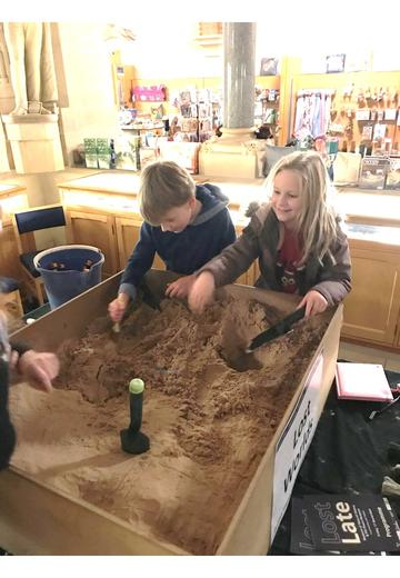 Two smiling children lean over a sandbox and use tools to scape the sand.