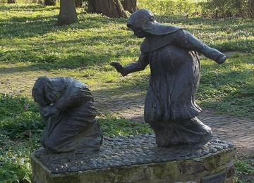 bronze statue of two religious sisters, one kneeling, one with a hand out standing