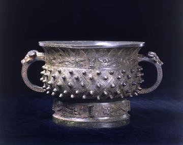 A bronze food basin, standing on a high foot with two handles, with bosses within diamond patterns. Just below the neck, around the body, is a band displaying dragons, and similar dragons decorate the foot.