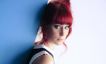 red haired woman leaning against blue and white background, stares at camera