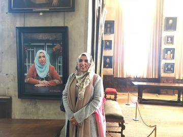 We are Bess at Hardwick Hall. Akeela Ahmed in front of her own portrait © National Trust - Gavin Repton, portraits by Rachel Adams, 2018