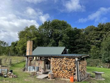 Photo of the Anagama kiln against a blue sky, with wood piled to one side.