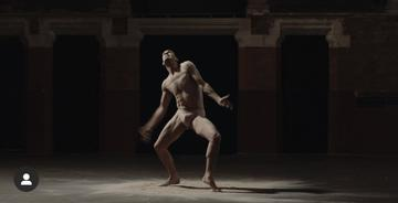 Image is a still photo from 'Jon's solo' dance performance depicting a dancer in the spotlight of an otherwise dark room. The body is in a pose as if attached to threads like a marionette.
