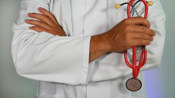 Doctor crossing his arms, holding a red stethoscope
