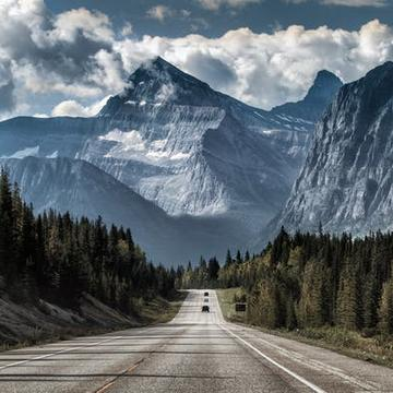 empty road with cars in the distance travelling toward fading mountains