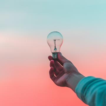 Hand holding light bulb in front of blue and red sky