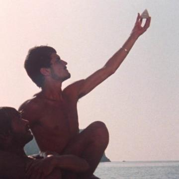 One topless man supports another holding a triangle up in the air on a sea-scape background.