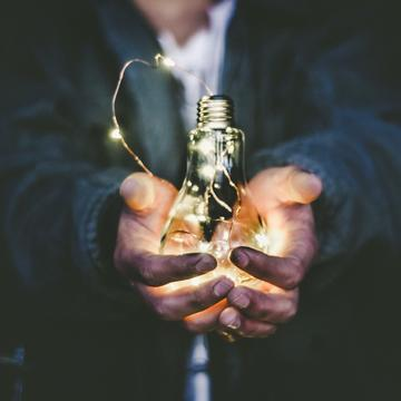 A lightbulb filled with fairylights held in someone's hands.