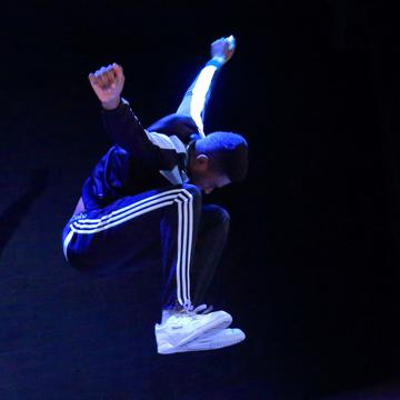 Man jumbing with arms outstretch on the side, wearing 3 stripped tracksuit