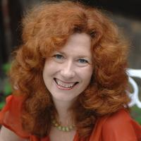 Red haired woman smiling at the camera with red top