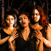 two women of colour hold and look at Medea (middle)who laments. White tribal markings on faces, wearing plain black clothing. Trees are in the background.