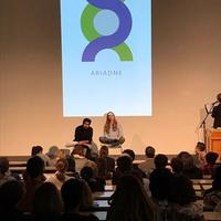 Two people sitting on a stage in front of an audience in a lecture hall with a genome logo projected on powerpoint behind them