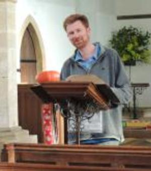 daniel crowther standing at a podium with a book inside a church