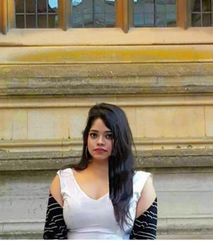 Ranjamrittika Bhowmik wearing white dress standing in front of building