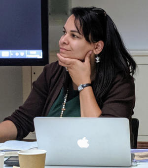 rosa andujar looking left wearing dark green, hand to chin,an apple laptop sits in front of her.